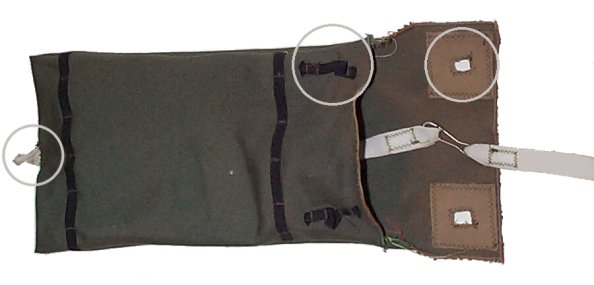 Circled, left to right, are the attachment for the pilot chute's bridle, the elastic loop that the suspension lines are placed through to keep the flap closed, and the hole in the flap.